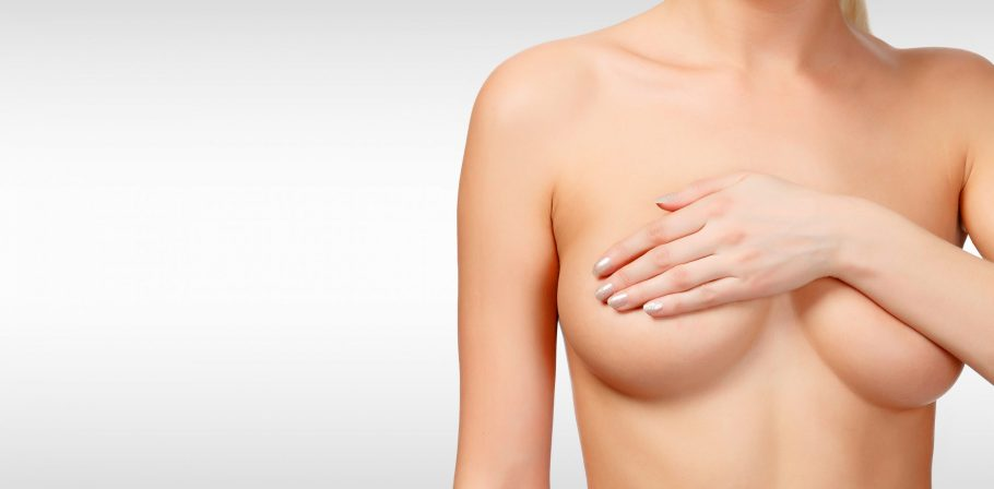 Woman controlling breast for cancer against a grey background with copyspace. Female healthcare con