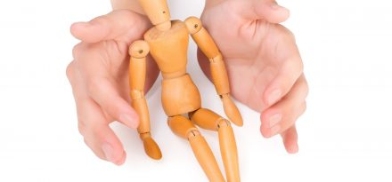 female hands covering wooden man