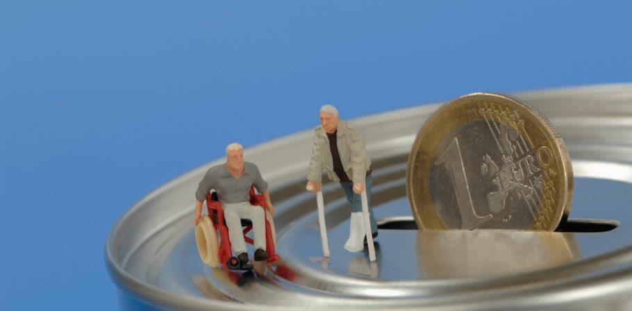 Kunststoff-Figuren, im Rollstuhl und mit Krücken auf Spardose